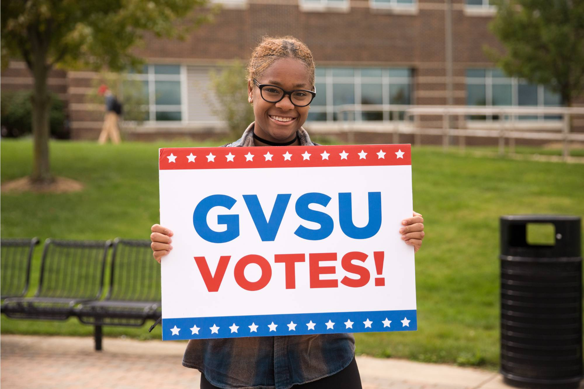 Girl holding up GVSU votes sign